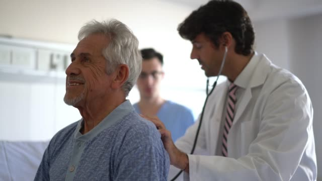 doctor checking the lungs of a hospitalized senior patient and giving the information to the nurse standing behind him - lung stock videos and b-roll footage