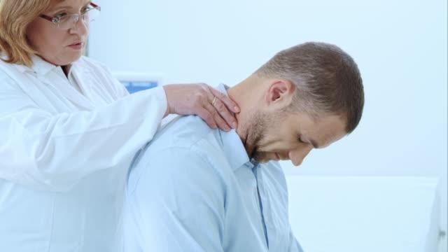 stockvideo's en b-roll-footage met doctor checking the male patients neck - masseren