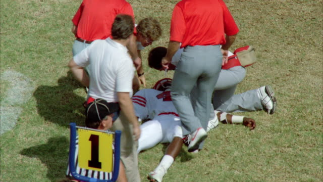 ms doctor checking to injured player - アメフトのユニフォーム点の映像素材/bロール