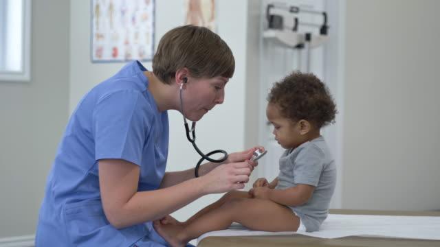 医師は赤ちゃんの心拍をチェックします - 小児科医点の映像素材/bロール