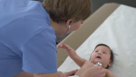 läkare kontrollerar spädbarn hjärtslag - kroppsvård bildbanksvideor och videomaterial från bakom kulisserna
