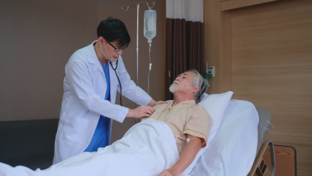 doctor come to visit patient in hospital room and talking about the disease of senior man. then use stethoscope to detect some symptom from patient - 人の肺点の映像素材/bロール