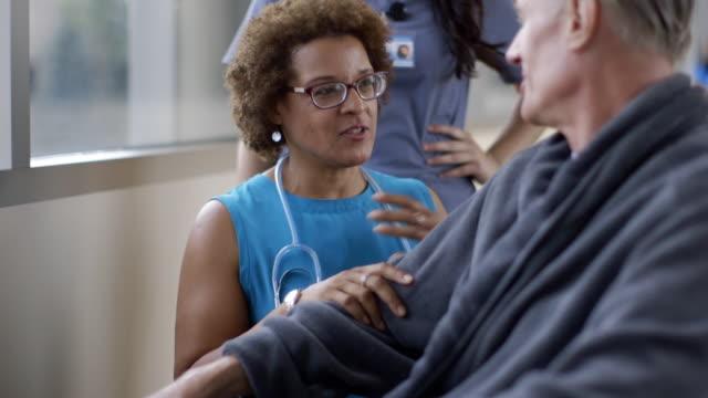 doctor comforting patient in wheelchair in hospital corridor - patient stock videos & royalty-free footage