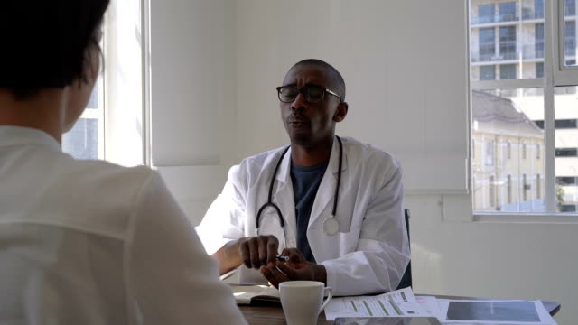 doctor communicating with patient in clinic - ascoltare video stock e b–roll