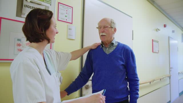 doctor consoling elderly patient in hospital corridor - medicare stock videos & royalty-free footage