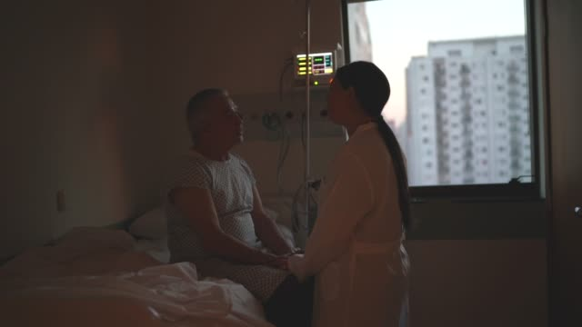 doctor consoling patient at hospital room - patience stock videos & royalty-free footage