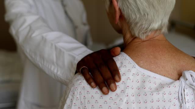 arzt consoling senior patientin im krankenhauszimmer - vertrauen stock-videos und b-roll-filmmaterial