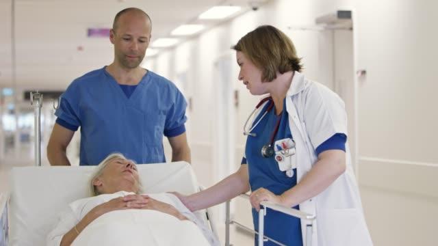 stockvideo's en b-roll-footage met doctor troostende senior patiënt op het ziekenhuis gurney - operatiekleding