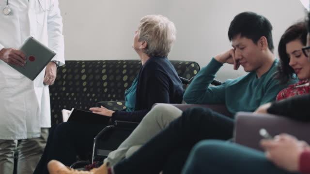 vídeos y material grabado en eventos de stock de doctor consulting patient in hospital waiting room - sala de espera edificio público