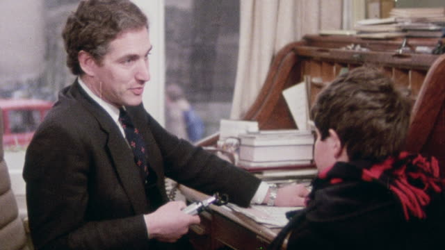 1982 montage doctor consulting with and examining throat of young patient / oxford, oxfordshire, england - boy medical exam stock videos and b-roll footage