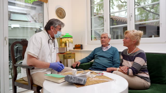 doctor counseling with a senior couple indoors - prescription medicine home stock videos & royalty-free footage