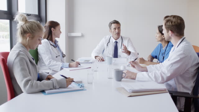 doctor discussing with colleagues in board room - coworker stock videos & royalty-free footage