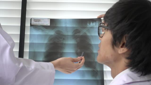 x線画像フィルムでボードルームで同僚と話し合う医師 - 腫瘍点の映像素材/bロール