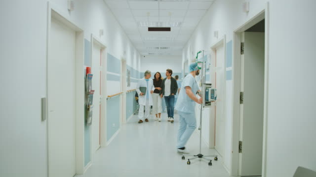 stockvideo's en b-roll-footage met arts bespreken met paar in hospital corridor - gang