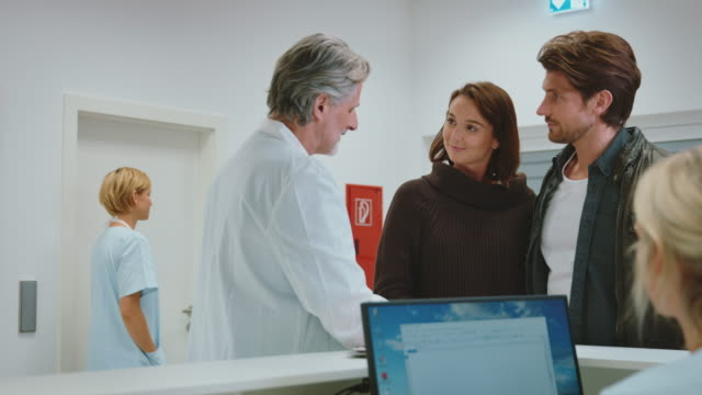doctor discussing with couple at reception desk - five people stock videos & royalty-free footage
