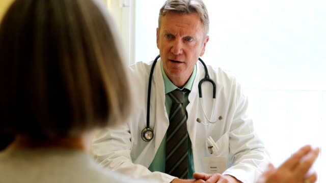 Doctor discussing with female patient at clinic