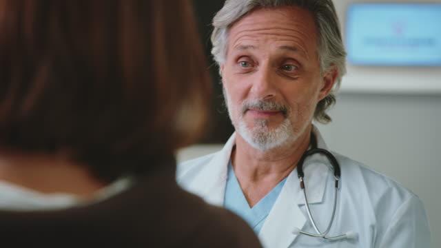 vídeos y material grabado en eventos de stock de médico discutiendo con el paciente en el hospital - edificio médico