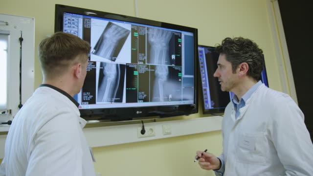 stockvideo's en b-roll-footage met arts bespreekt röntgen resultaten in office met een collega - medische röntgenfoto