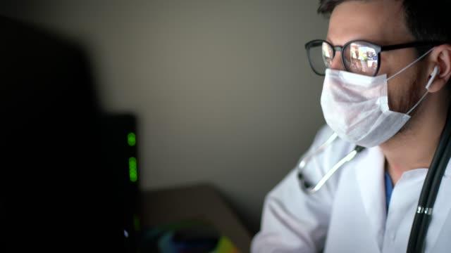 vidéos et rushes de docteur faisant un appel vidéo sur l'ordinateur au bureau du médecin - cabinet médical