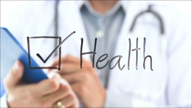 vídeos y material grabado en eventos de stock de médico haciendo un examen médico y escribir en el bloc de notas - material médico