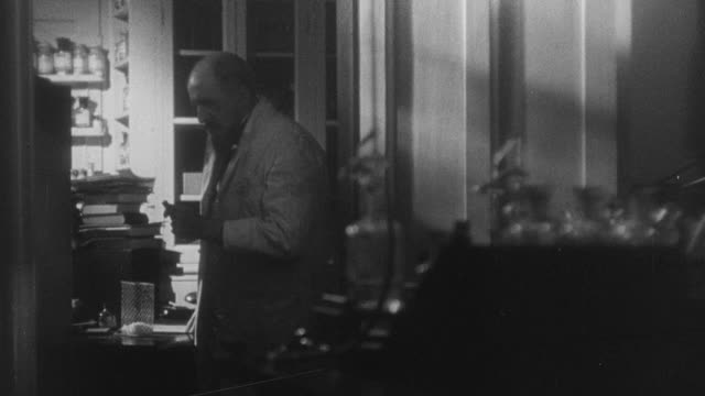 1941 reenactment doctor emil von behring in his office and laboratory, discovering a treatment using anti-toxins for diphtheria / united kingdom - diphtherie stock-videos und b-roll-filmmaterial