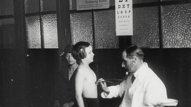 1925 montage doctor examines student's throat and listens to her chest with stethoscope while fellow students have their height measured, head bandaged, and eyes bathed by nursing sisters in school infirmary / newcastle upon tyne, england, united kingdom - boy medical exam stock videos and b-roll footage