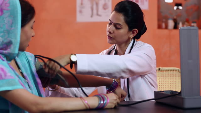 Doctor examining a adult woman with a blood pressure gauge