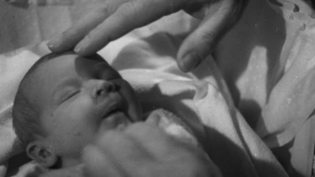 1955 MS Doctor examining a baby / United Kingdom