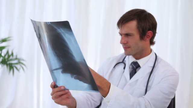 doctor examining a chest xray and then looking at camera - chest torso stock videos & royalty-free footage