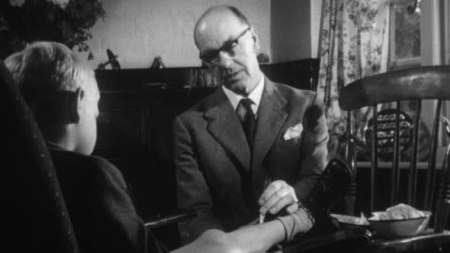 1955 montage doctor examining a young patient / united kingdom - 1955 video stock e b–roll