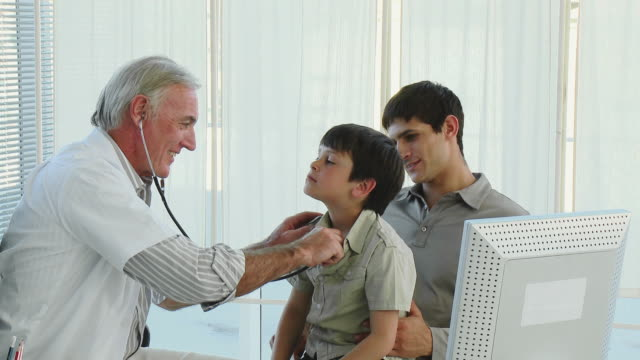 MS Doctor examining boy (8-9), accompanied by father / Cape Town, South Africa