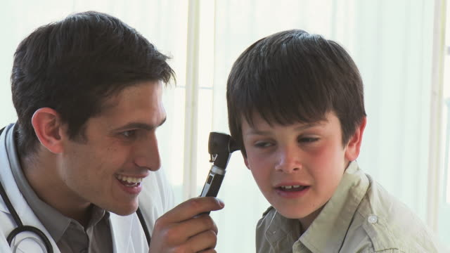 CU Doctor examining boy (8-9) using otoscope / Cape Town, South Africa