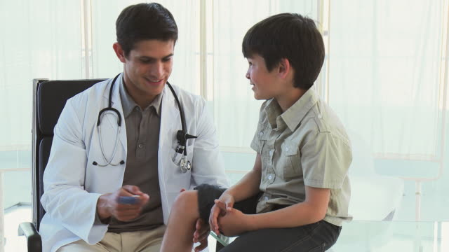 ms doctor examining boy (8-9) using reflex hammer / cape town, south africa - boy medical exam stock videos and b-roll footage