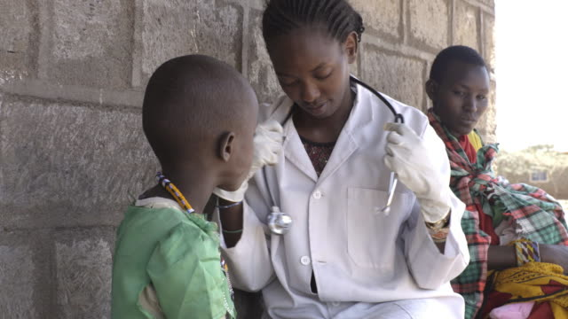 doctor examining child patient at clinic. kenya, africa - fürsorglichkeit stock-videos und b-roll-filmmaterial