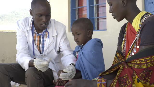 vídeos y material grabado en eventos de stock de doctor examining child patient. kenya, africa. - países en vías de desarrollo