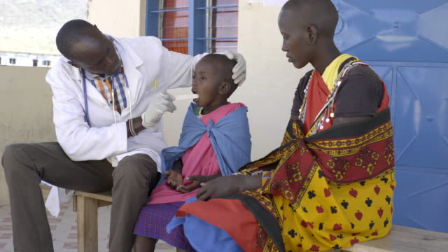 Doctor examining child patient. Kenya, Africa.