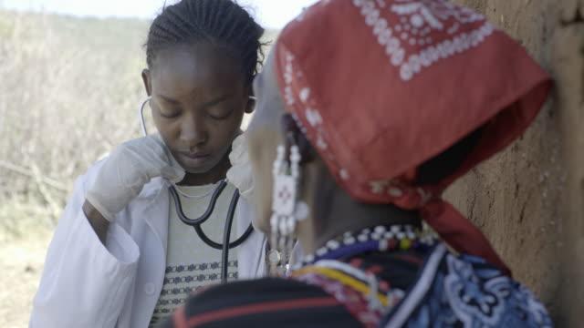 Doctor examining elderly patient in rural village. Kenya, Africa.