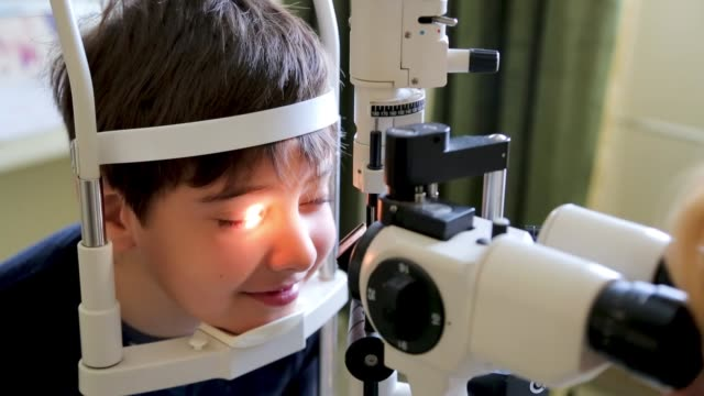doctor examining eyesight of cute kid, eye examination at slit lamp in oculist office - clinic stock videos & royalty-free footage