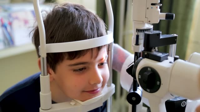 doctor examining eyesight of cute kid, eye examination at slit lamp in oculist office - ophthalmologist stock videos and b-roll footage