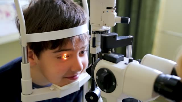 doctor examining eyesight of cute kid, eye examination at slit lamp in oculist office - lens optical instrument stock videos & royalty-free footage