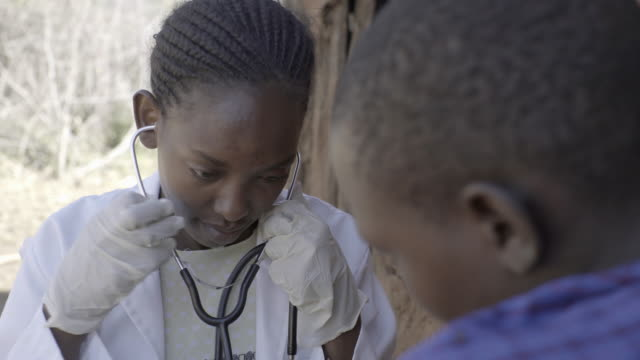doctor examining female patient in rural village. kenya, africa. - listening to heartbeat stock videos and b-roll footage