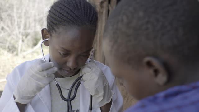 Doctor examining female patient in rural village. Kenya, Africa.