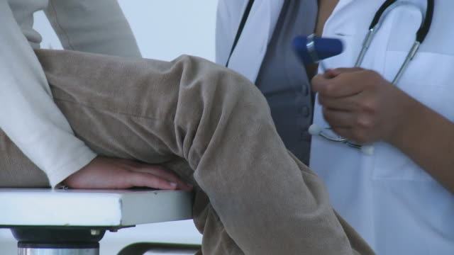 CU Doctor examining girl (8-9) using reflex hammer / Cape Town, South Africa