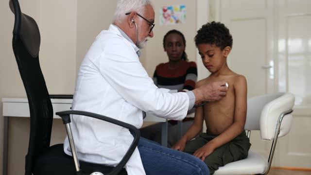 vidéos et rushes de docteur examinant les poumons et le battement de coeur de petits garçons - examen