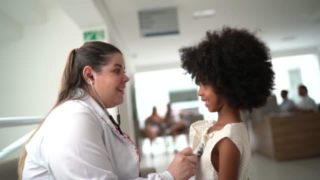 vídeos de stock e filmes b-roll de doctor examining little cute girl at hospital - estetoscópio