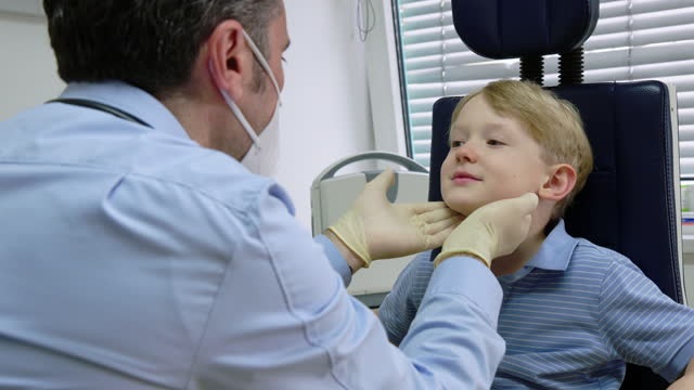 doctor examining little patient's neck - examining stock videos & royalty-free footage