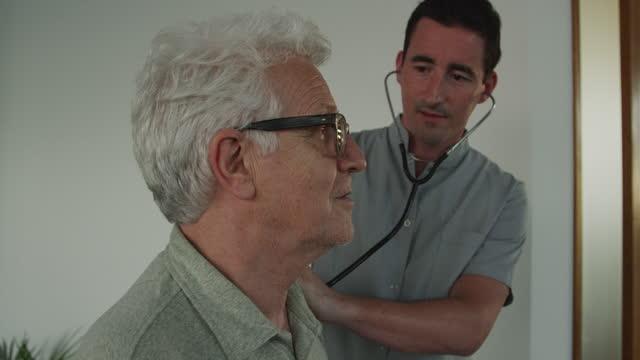 vídeos y material grabado en eventos de stock de médico examina a paciente masculino con estetoscopio en sala de estar durante covid - 19 pandemias - estetoscopio