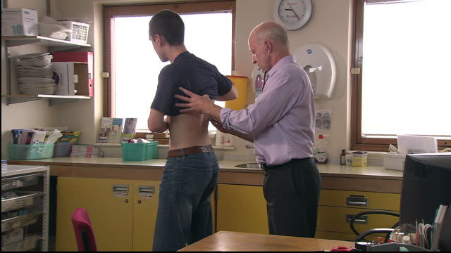 MS, Doctor examining male patient's back in office
