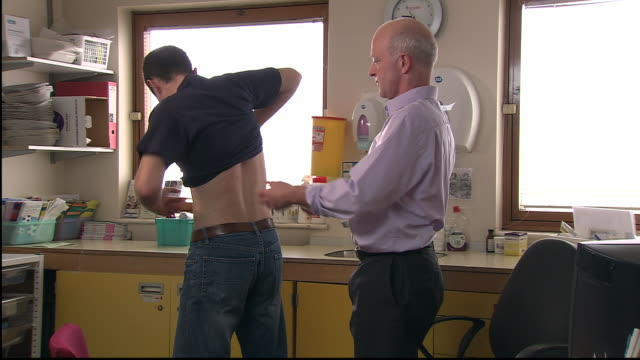 ms, doctor examining male patient's back in office - dorso umano video stock e b–roll