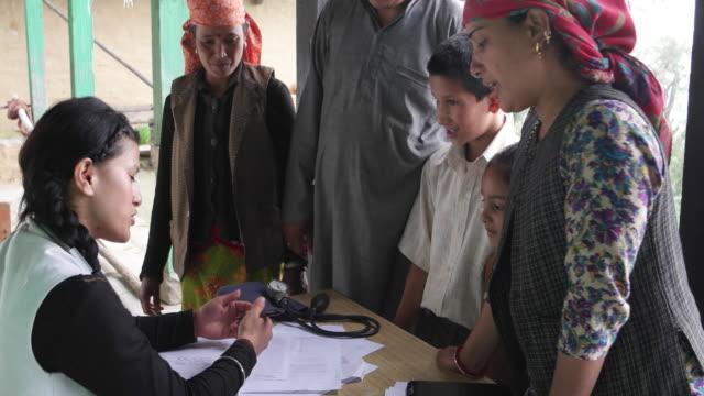 vídeos de stock, filmes e b-roll de doctor examining patiences and giving consultancy advice - pobreza questão social